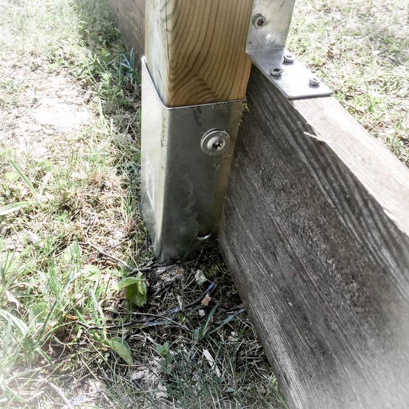 Vinkeljärn för att fästa stolpe med reglar. Vi lade sedan tunga stenar längs med nedre brädan.